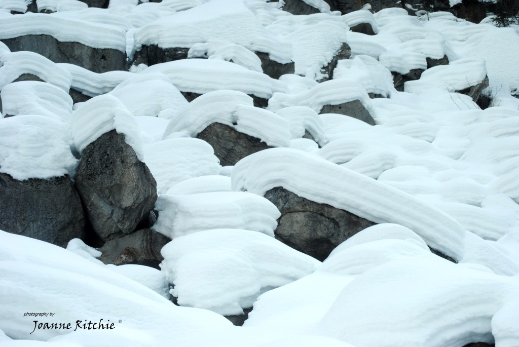 Layers of snow on the river rocks